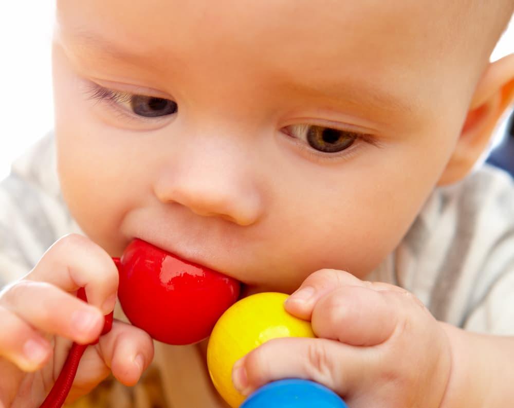 Baby nuckelt am Spielzeug © Robert Kneschke, stock.adobe.com