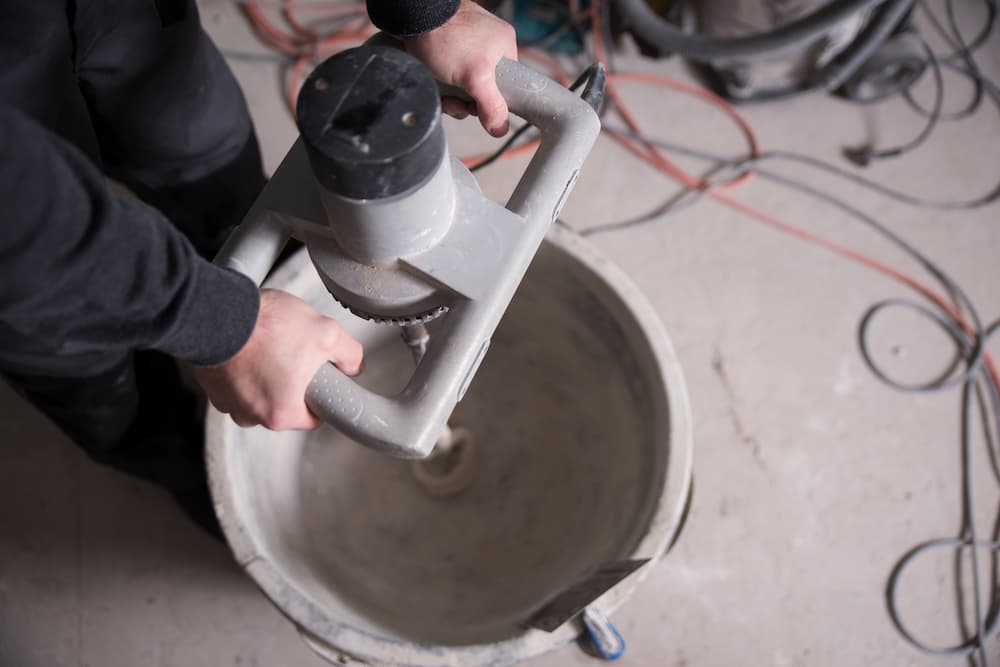 Handwerker arbeitet auf einer Baustelle mit einem Rührgerät © Wellnhofer Designs, stock.adobe.com