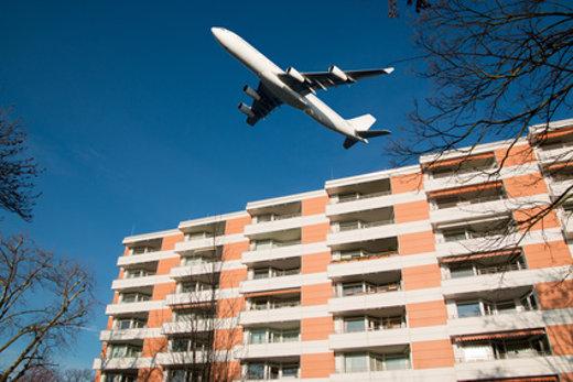 Flugzeug fliegt über Mehrfamilienhaus © mitifoto, fotolia.com