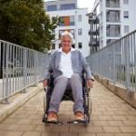 Lachende Seniorin im Rollstuhl auf einer Rampe vor Gebäude