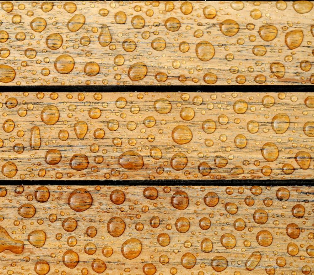 Von einer gewachsten Holzoberfläche perlt das Wasser ab © montebelli, stock.adobe.com