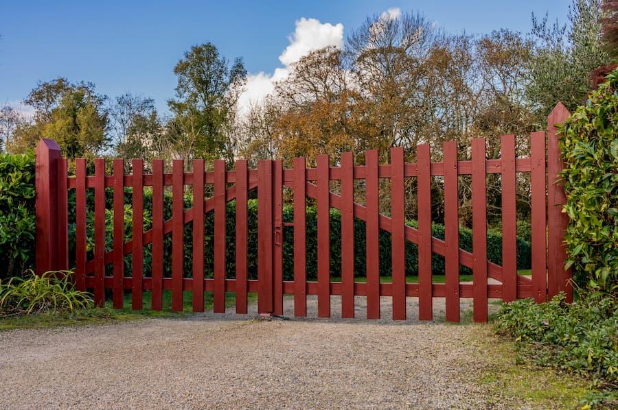 Rotes Holztor im Gartenbereich mit Leinölanstrich © fotoschlick, stock.adobe.com